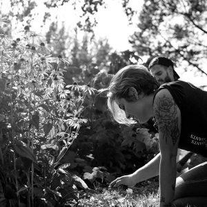 Une fille arrache des mauvais herbes à travers des fleurs
