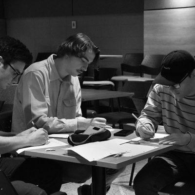 Trois étudiants en train d'écrire