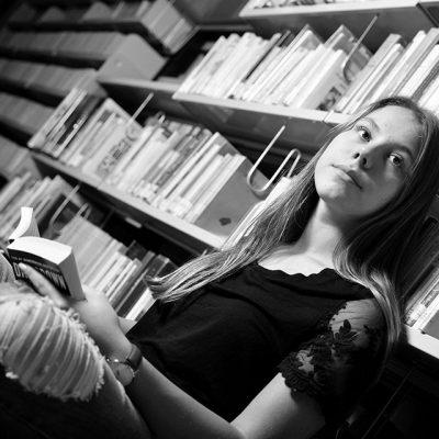 Fille assise dans les rangées de la bibliothèque