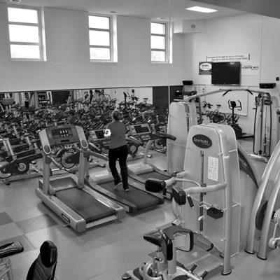 Une personne qui coure sur un tapis roulant dans la salle d'entraînement