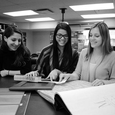 Trois étudiantes consultent des échantillons de matériaux