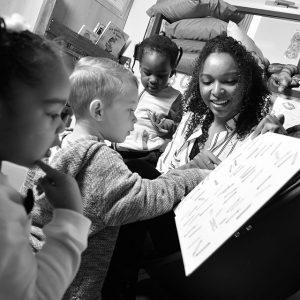 Étudiante présentant un livre à des enfants