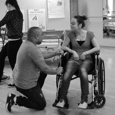 Un étudiant discute avec une autre étudiante en chaise roulante